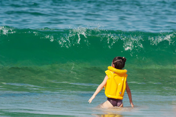 A little girl in a yellow life jacket stands in front of a big wave