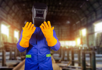 Welder in orange gloves and mask standing in factory.