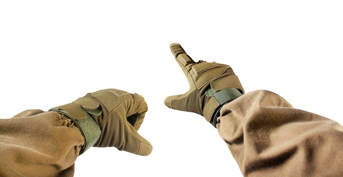 Isolated photo of first person view soldier hands in tactical gloves pointing gesture.