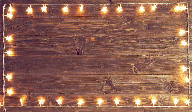 Merry Christmas! Christmas lights frame on wooden background with copy space