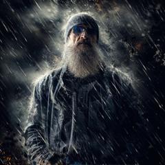 Artistic portrait of a bearded male in the rain