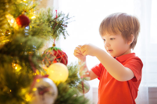 Xmas party celebration. Child decorating Christmas tree at home. Family with kids celebrate winter holidays. New year small boy at decoration toy