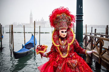 Masked Venetian Performer on Wooden Pier by Gondola in Venice, Italy