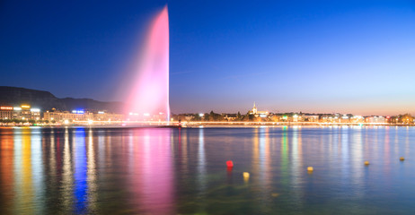 Geneva city lights at night . Pink fountain is reflected in still lake in the evening. Colorful long exposure and blurred buoys on the surface. Fototapete