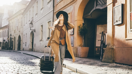 Female going with travel luggage at the narrow street between residential buildings in European town. Young girl rolling suitcase down on the cobblestone pavement and checking route on the paper map