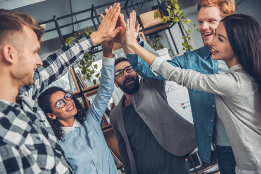 Startupers working at office together standing giving high five success