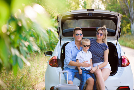 Couple with son having a coffee break while traveling in the countryside. A man and a woman are sitting in the trunk of a car and rest.