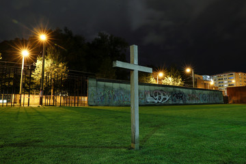 A long exposure picture shows a cross in front of remains of the Wall at the Berlin Wall memorial on Bernauer Strasse at night in Berlin