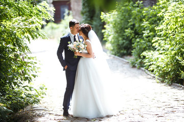 The bride and groom walk together in the park. Charming bride in a white dress, the groom is dressed in a dark elegant suit. Pretty bride and stylish groom. Wedding day. Marriage.