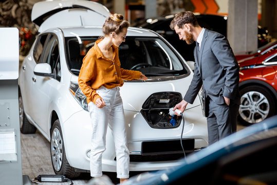 Sales manager with client near electric car at the car dealership