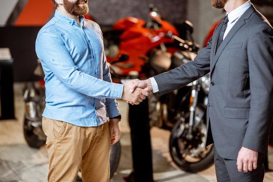Handshake in the showroom with motorcycles