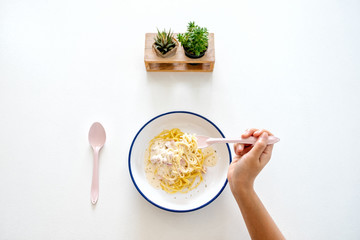 Top view image of a woman eating carbonara spaghetti on the table