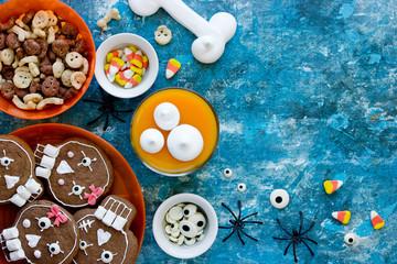 Halloween sweets and treats - skull cookies, candy corn, pumpkin panna cotta, meringue bones top view Fototapete