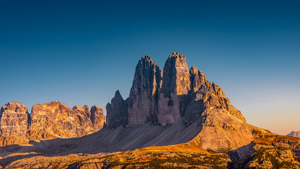 Panoramic view over beautiful sunset in magical Three Dolomite peaks at the national park Three Peaks (Tre Cime, Drei Zinnen) in Autumn October colors at blue sky, South Tyrol, Italy
