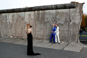 A gay couple pose for their wedding pictures in front of a section of Wall at the Berlin Wall memorial on Bernauer Strasse in Berlin
