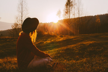 A dreamy young girl or woman traveler in a fedora hat sits in the grass and enjoys the mountain view, the warm rays of the autumn sun and a beautiful sunset.