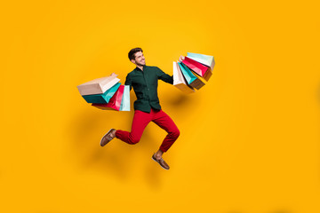 Full length body size photo of cheerful positive handsome jumping man holding numerous packages...