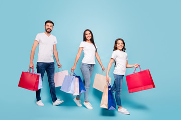 Full length photo of beautiful three people clients mom dad schoolkid with brown hair shop hold bags bargain black friday wear white t-shirt denim jeans sneakers isolated over blue color background