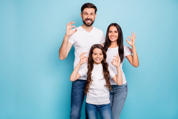 Portrait of positive content three promoters mom dad offspring with brunet hair show ok sign...