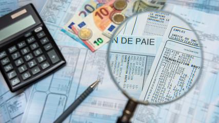 Bulletin de paie français à la loupe, avec argent en euros, calculette et stylo - fototapety na wymiar