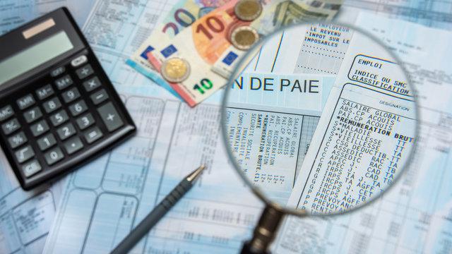 Bulletin de paie français à la loupe, avec argent en euros, calculette et stylo