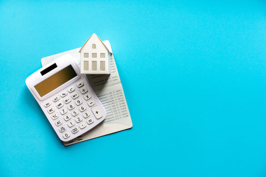 close up top view group of calculator , home model and banking account book on blue color background with space for financial loan concept