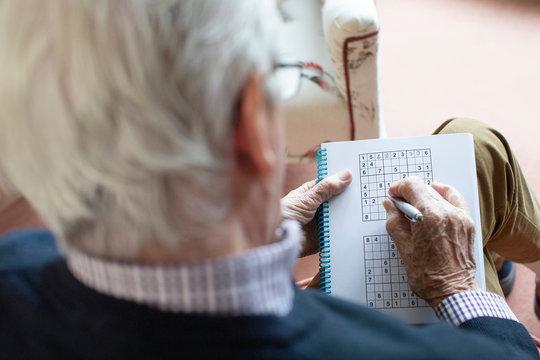 Senior Man Doing Sudoku Puzzle At Home