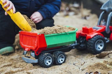 Closeup shot of a toddler playing with sand and construction toys in the park during daytime