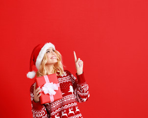 happy young cheerful girl laughs and jumps in christmas hat and with  gift on  red   background.