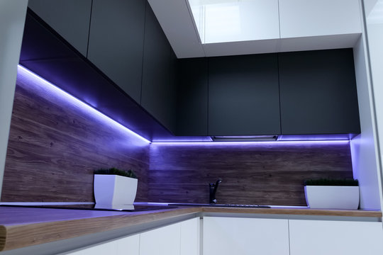 black ergonomic cupboards decorated with amazing violet neon strip light above wooden kitchen set surface