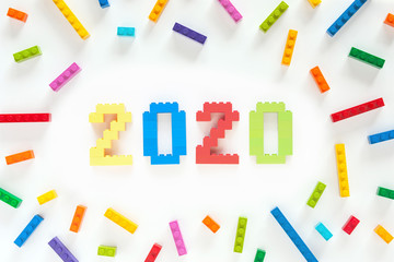 Numbers 2020 made from toys blocks with scattered blocks on white background