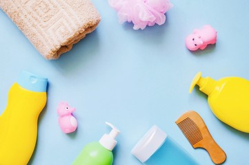 Flat lay photo baby shampoo, shower gel, liquid soap, wooden comb, sponge, towel and rubber toys on a light blue background