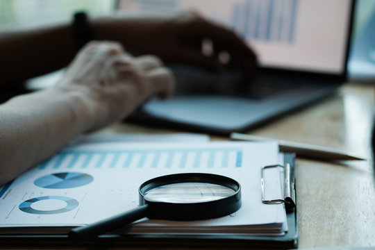 Businessman looking through a magnifying glass to documents. Business assessment and audit. Magnifying glass on a financial report. Concept of search.
