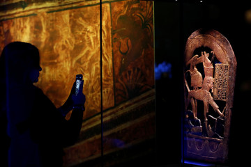 "A woman takes a picture of a wooden Traveling Chest of Tutankhamun during the media preview of ""Tutankhamun: Treasures of the Golden Pharaoh"" exhibition set to open at the Saatchi Gallery"