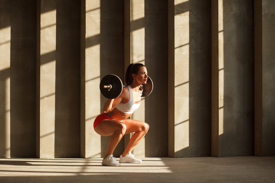beautiful athletic woman doing squats with barbell near concrete wall in gym