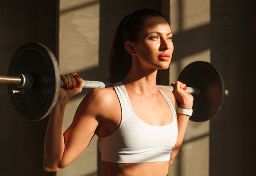 beautiful sportive woman with barbell on shoulders in gym, close up portrait, natural light