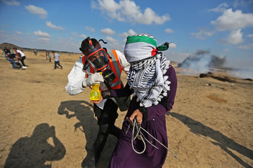 Medic helps a Palestinian demonstrator affected by tear gas during an anti-Israel protest in the southern Gaza Strip