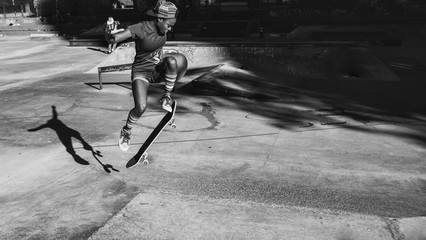 Young girl performing tricks with the skateboard in a skate park
