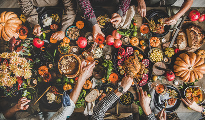 Family celebrating Thanksgiving day. Flat-lay of eating and pouring wine peoples hands over...