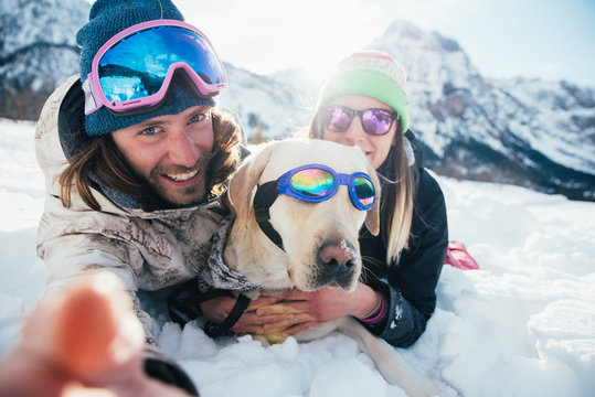 couple playing with dog on the mountains, on the snowy ground