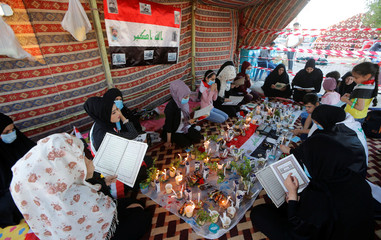 Demonstrators read Quran and light up candles during an anti-government protest in front of governement building in Basra