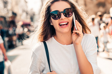 Young stylish woman using phone walking on the street, wearing trendy outfit. Wall mural