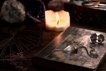 Still life with burning candle on old wooden table top, black fortune teller card, magic book and pentagram box