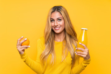 Young blonde woman holding an orange juice over yellow background