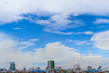 White fluffy clouds flying on the fresh blue sky after hard raining over group of building and house with copy space. Background for business target or meteorology or inspiration.