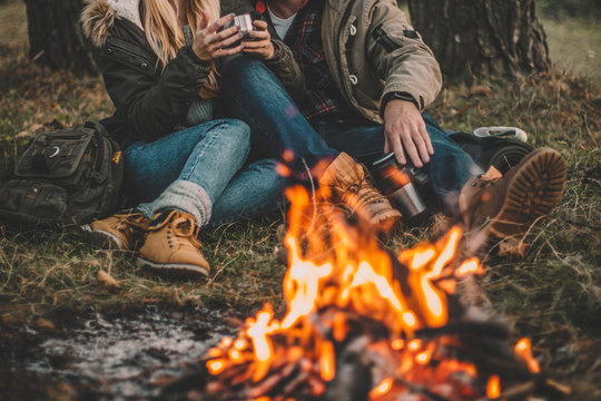 Traveler couple camping in the forest and relaxing near campfire after a hard day. Concept of trekking, adventure and seasonal vacation.