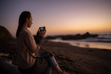 Woman taking picture of a sunset near ocean