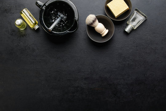 Shaving accessories set on a dark background, top down view