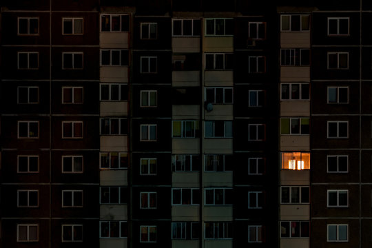 light in a single window. Flat night panorama of multicolor light in windows of multistory buildings. life in big city