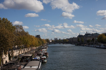 View of  river in Paris France riverwalk boats lined up blue cloudy sky